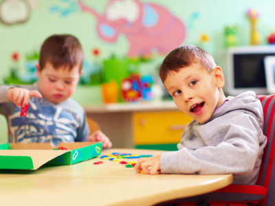 cute kids with special needs playing with developing toys while sitting at the desk in daycare center